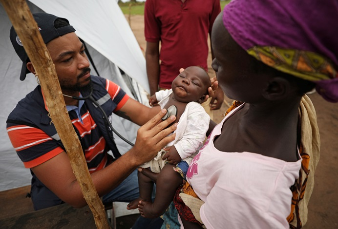 A doctor examines a child at a camp for people displaced in flooding in the aftermath of Cyclone Idai, near Beira, Mozambique.  REUTERS/Mike Hutchings, please do not reuse.