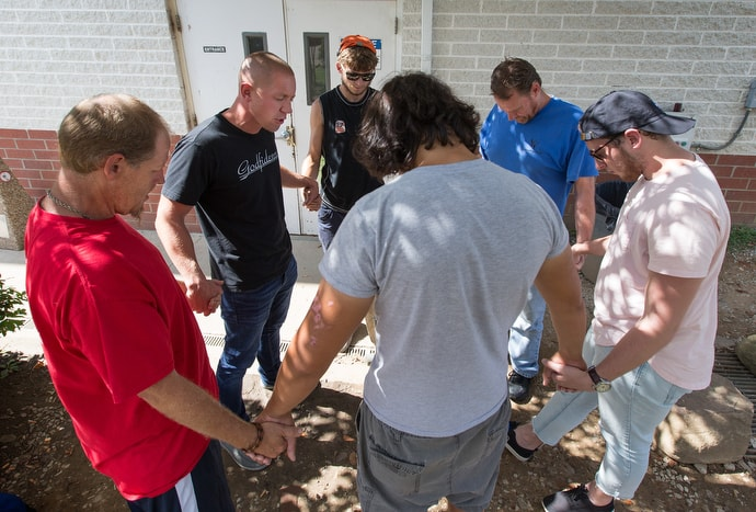The Rev. Ross Thornton (second from left) and Jasen Thaxton (right) pray with clients of the city mission in Huntington, W.Va. Thaxton is a lay minister and friend of Thornton's. Photo by Mike DuBose, UMNS.