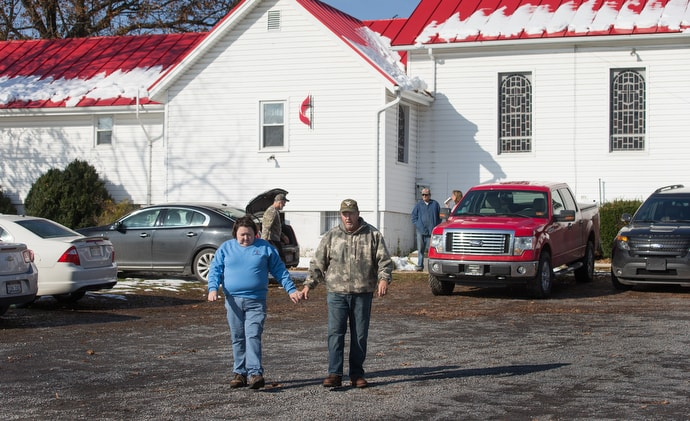 The Revs. Cheryl and Harold George walk out of Oak Grove United Methodist Church in Fisher, W.Va., on their way to deliver meals in the neighborhood. Both are EMTs who have seen the effects of the opioid crisis firsthand. Photo by Mike DuBose, UMNS.