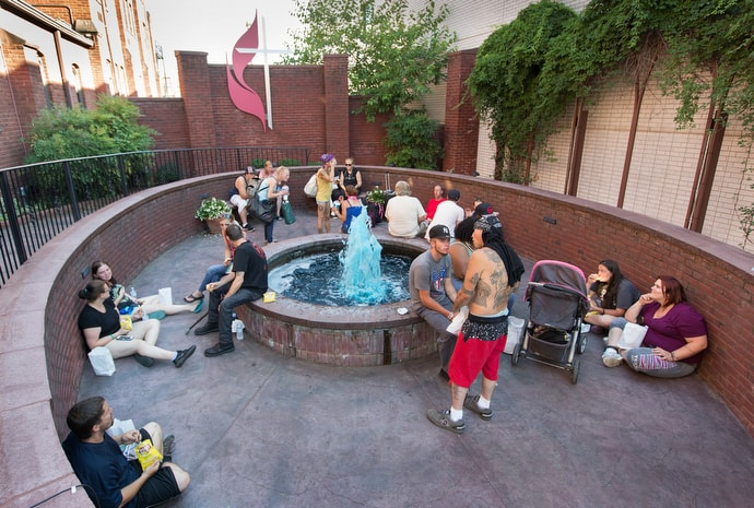Community members gather for a weekly meal and prayer support in the courtyard at Johnson Memorial United Methodist Church in Huntington, W.Va. Photo by Mike DuBose, UMNS.