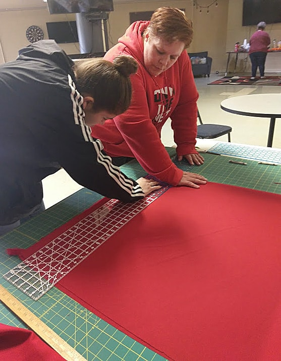 Red fabric is carefully measured as a first step in sewing a red shawl to honor murdered and missing indigenous women at Chemawa Indian Boarding School in Salem, Oregon. Photo by A. Wolf.