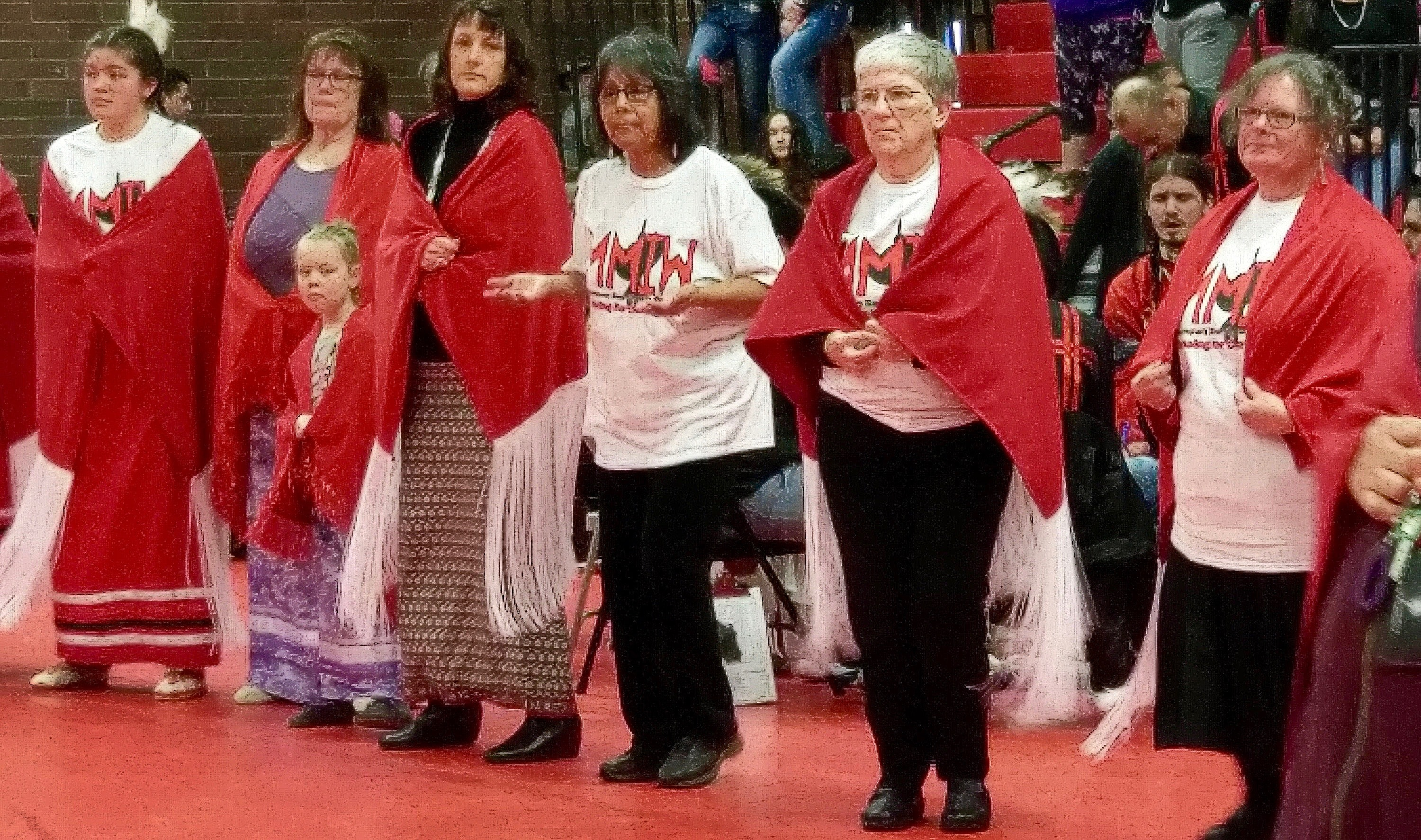 Women from Morningside United Methodist Church in Salem, Oregon, wear red shawls they helped to create during a dance to honor murdered and missing indigenous women at Chemawa Indian Boarding School. Photo by A. Wolf.