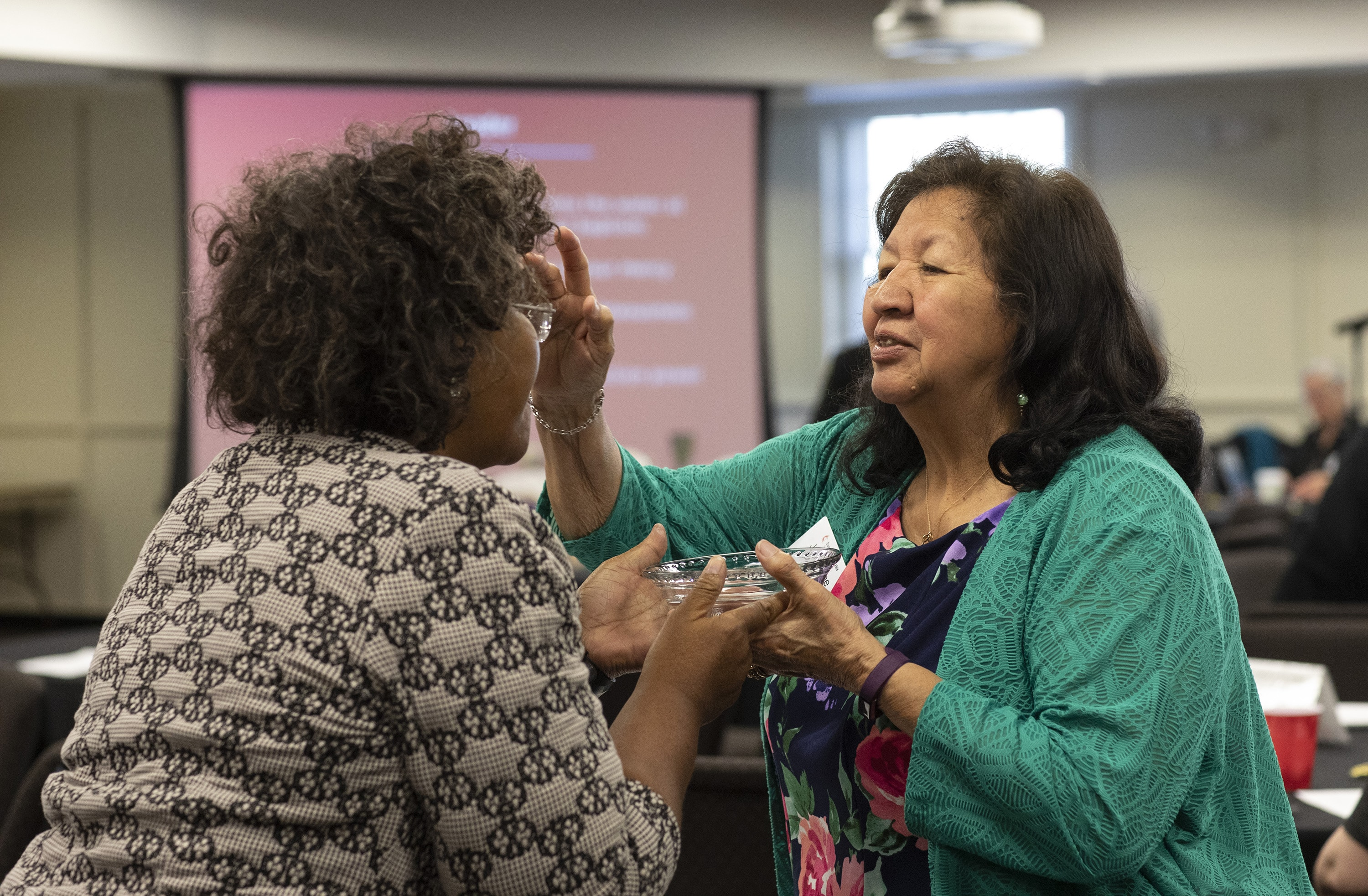Josephine Deere, right, blesses fellow Connectional Table member Benedita Penicela Nhambiu during a service of baptism remembrance on April 3 at the Connectional Table meeting in Nashville, Tenn. Photo by Kathleen Barry, UMNS.