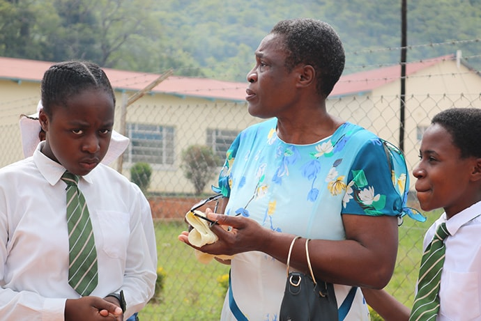 Edina Ngwenya, Textile Technology and Design teacher at Hartzell High School in Mutare, Zimbabwe, surveys the damage with two of the students. Photo by Priscilla Muzerengwa, UMNS.