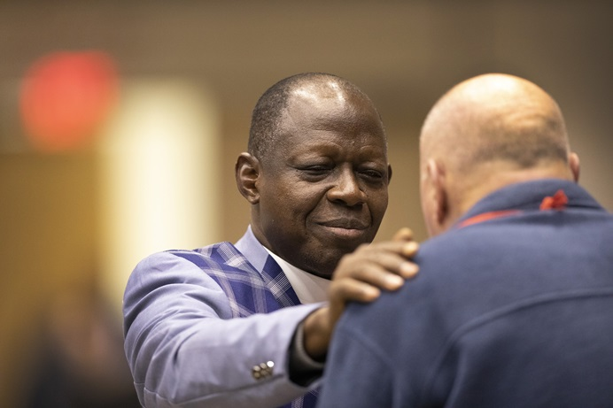 Bishop John K. Yambasu prays with the Rev. Byron Alexander, a conference page, during the 2019 General Conference in St. Louis. Photo by Kathleen Barry, UMNS.