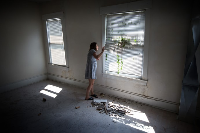 """Ann Hammond looks out an overgrown window of a home she hopes to turn into a recovery house for women living with addiction. The house is on the grounds of United Methodist Temple in Clarksburg, W.Va. """"Fundraising is slow but we're getting there, slowly but surely,"""" she said. Photo by Mike DuBose, UMNS."""