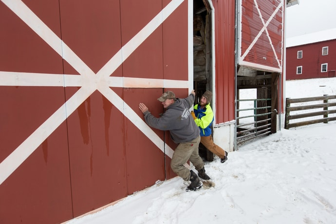 Jim (right), a recovering addict, helps Mark Utterback open an icy barn door at Brookside Farm, part of the Jacob's Ladder rehabilitation program in Aurora, W.Va. Utterback is director of farming for the program. Photo by Mike DuBose, UMNS.