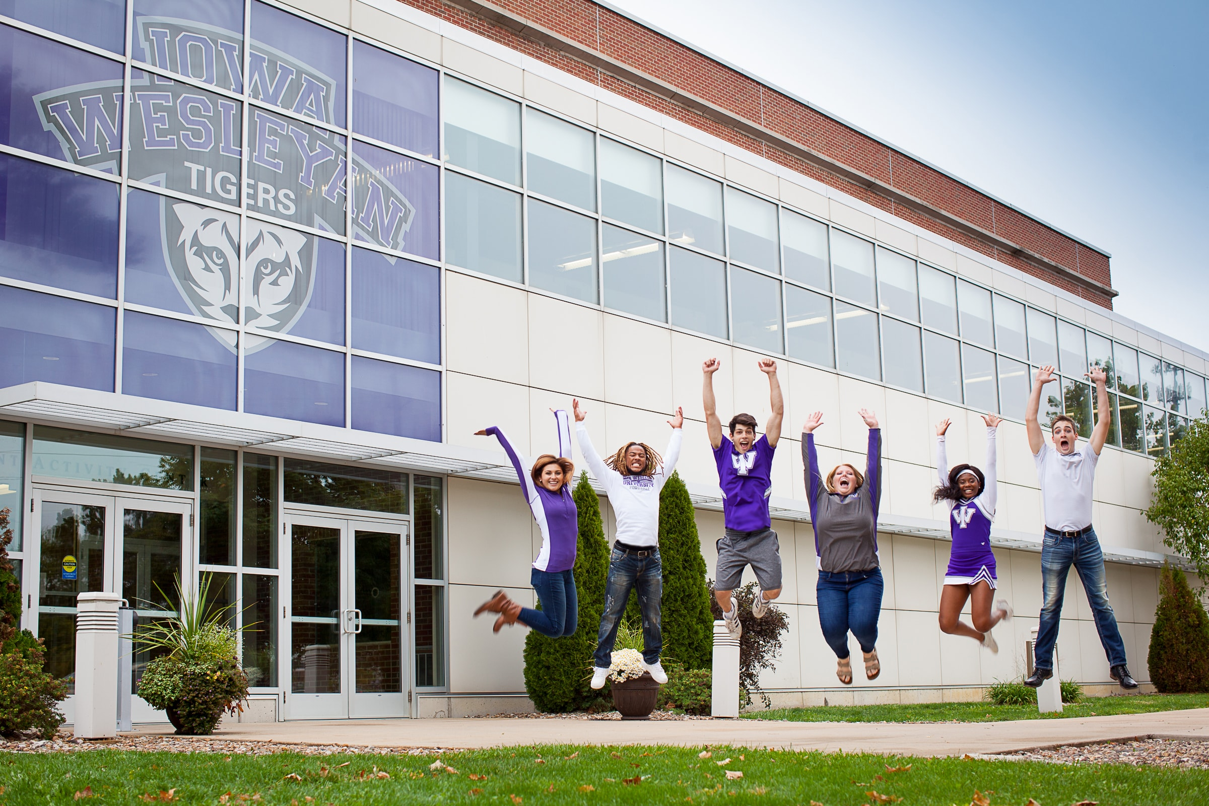 Students from Iowa Wesleyan University jump in this campus shot in Mount Pleasant, Iowa. Photo courtesy of Iowa Wesleyan University.