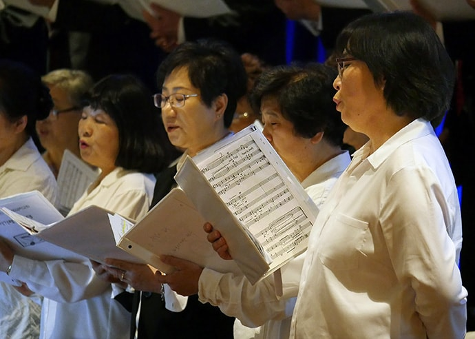 Members of the Hallelujah Choir of First Korean United Methodist Church in Wheeling, Ill., rehearse ahead of opening worship at the Council of Bishops meeting in Chicago. Photo by Heather Hahn, UMNS.