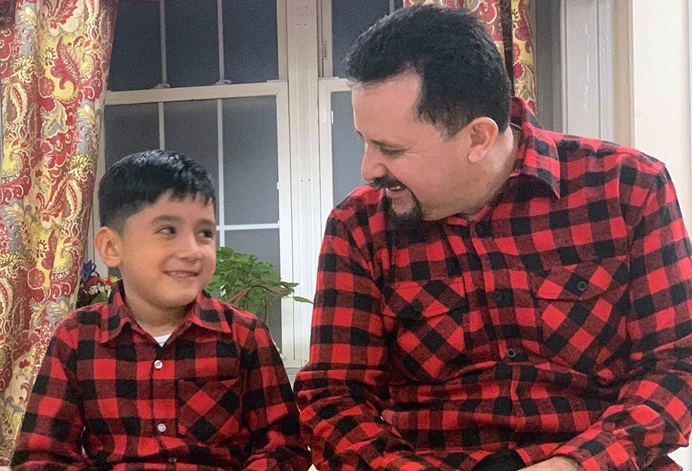 """Nelson Pinos sits with his son, Brandon Pinos, age 6, in the fellowship hall of First and Summerfield United Methodist Church in New Haven, Conn. Pinos, who has lived in the U.S. for 26 years, is currently living in sanctuary at the church. Image courtesy of the """"Keep Nelson Home"""" Facebook page."""