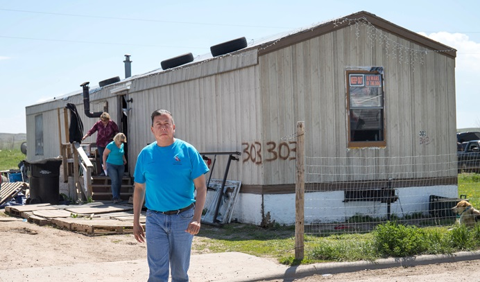 The Rev. David Wilson from the Oklahoma Indian Missionary Conference visits a home damaged by two recent snowstorms and subsequent flooding on the Pine Ridge Indian Reservation in South Dakota. Photo by Ginny Underwood, UM News.