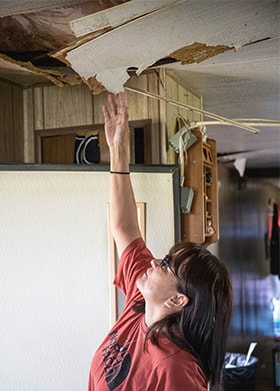 Susan Shangreaux, a resident on the Pine Ridge Indian Reservation, points to a spot on her ceiling that caved in from heavy snow after severe winter storms. Photo by Ginny Underwood, UM News.