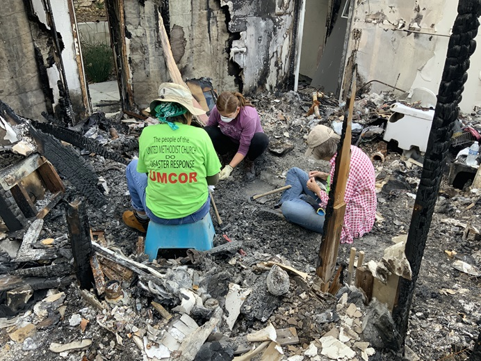 From left, United Methodist Committee on Relief volunteer Helen Quirocho, Magnolia Becker and UMCOR's Judy Lewis sift through wildfire wreckage in what is left of Becker's home in the Truncas canyon of Malibu, California, on April 6, 2019. Photo by Doug Lewis.