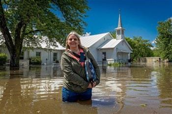 Shelli Pleasant, pastora da Igreja Metodista Unida Avant, fica em frente à igreja com água até as coxas, um dia depois que uma série de tempestades em 20 de maio resultou em enchentes quase históricas da cidade. Foto de John Pleasant, Conferência Anual de Oklahoma.