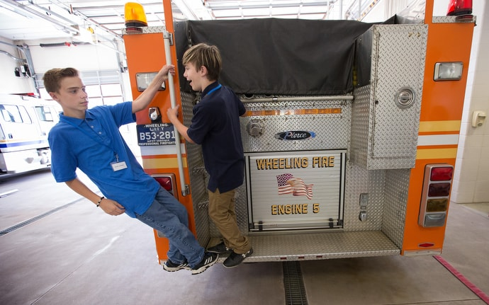 Skyler (left) and Cameron climb on the tailboard of a fire engine during a field trip to Fire Station 5 in Wheeling, W.Va. They were taking part in House of the Carpenter's Pre-Work Camp. Photo by Mike DuBose, UM News.