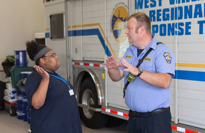 Zariah (left) visits with Lt. Bill Wagner at Fire Station 5 in Wheeling, W.Va. during a field trip for students in House of the Carpenter's Pre-Work Camp. Photo by Mike DuBose, UM News.