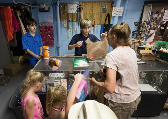 opioids-ministry-with-children-8-thrift-store Cameron (center) bags purchases for a family in the thrift store at House of the Carpenter in Wheeling, W.Va. Photo by Mike DuBose, UM News.