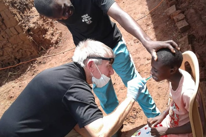 The Rev. Tom Wall, a United Methodist campus minister at the University of South Carolina, brushes a boy's teeth during a free health camp in eastern Uganda. The United Methodist Church in Uganda and the African Methodist Episcopal Church jointly sponsored the weeklong event. Wall served as the team leader of the group from the United States. Photo by Vivian Agaba, UM News.
