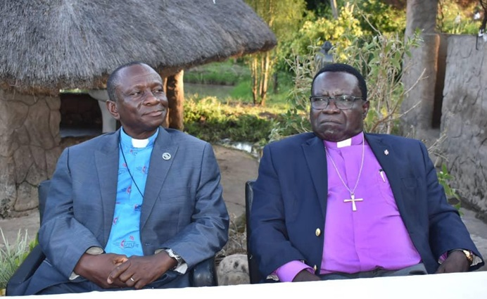 The Rev Alan Masimba Gurupira, administrative assistant to Bishop Eben K. Nhiwatiwa, sits next to South Congo Bishop Owan Kasap at a farewell dinner at Bouche Camp in Lubumbashi, Congo. A delegation of 12 lay and clergy members from the Zimbabwe Episcopal Area traveled to South Congo to exchange ministry ideas and strategies for church growth. Photo by Chenayi Kumuterera, UM News.