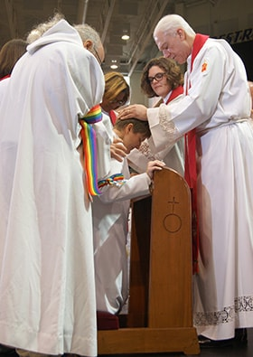 Bishop Thomas J. Bickerton (right) ordains the Rev. Lea Matthews as a deacon in full connection during the New York Annual Conference meeting. Also pictured, from right, are the Revs. K Karpen, Denise Smartt Sears and Heather Sinclair. Photo by Stephanie Parsons, NYAC.