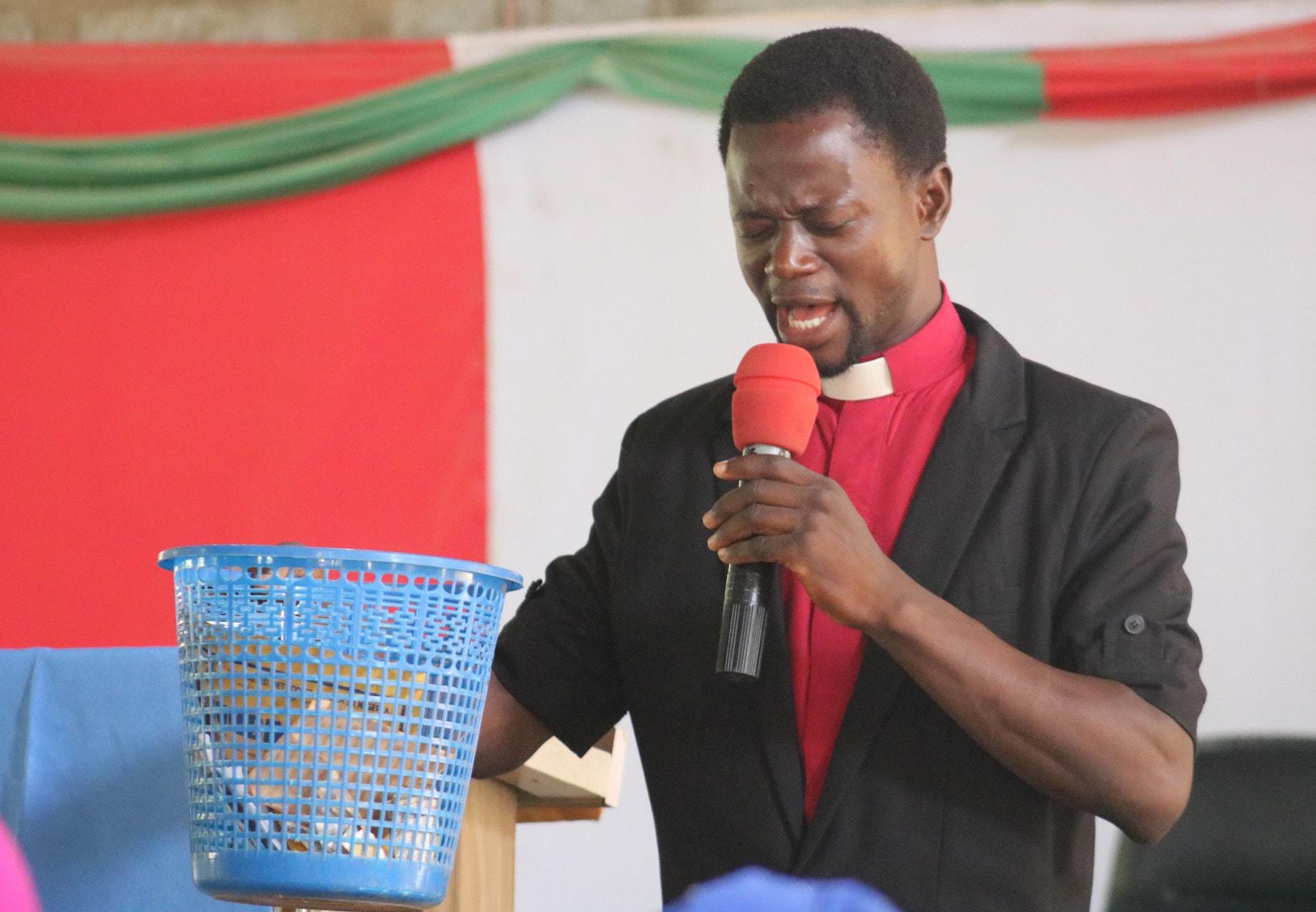 The Rev. Karabi Moodi, associate pastor at Abuja Area 1 United Methodist Church, prays over the Sunday offering on June 2, 2019.   Photo by E Julu Swen, UM News.