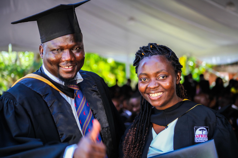 클로딘 미기샤 (우측)가 짐바브웨이 무타레에 위치한 아프리카대학교를 졸업하면서, 웨남 다발레씨로부터 축하를 받고 있다. 콩고의 고마 출신인 미기샤는 아프리카대학교 개교 25주년을 맞는 2019년의 졸업생 중 한 명이다. 다발레씨는 이 학교의 국제학생처장이다. 사진 제공, 아프리카대학교.