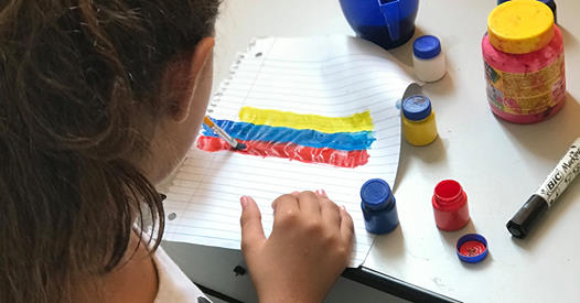 Hailey pinta una bandera venezolana durante el tiempo de clases de  artes y manualidades, con niños/as del refugio en Boa Vista. Foto: Emily Everett, GBGM.