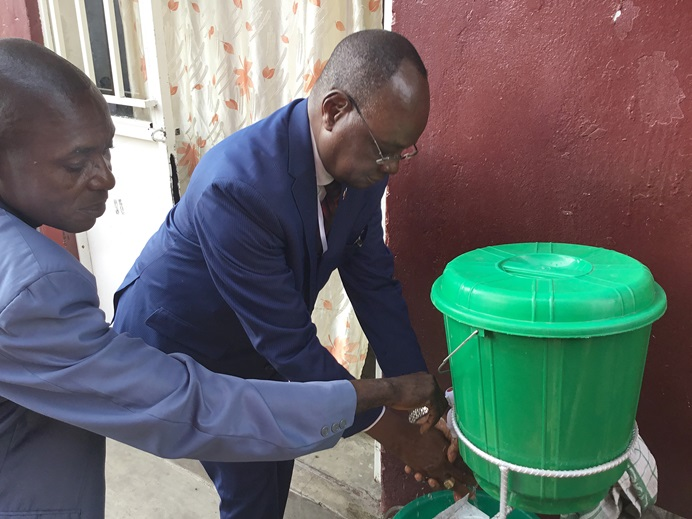 Bishop Gabriel Yemba Unda washes his hands during the Kivu Annual Conference in Goma, Congo. Unda invited conference speakers to observe five minutes of prayer for those affected by the region's Ebola outbreak, which began last August. Photo by Philippe Kituka Lolanga, UM News.