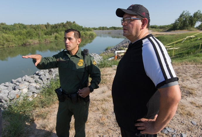 U.S. Border Patrol Agent Robert Rodriguez (left) shows the Rev. Robert Lopez an unfenced section of the U.S.-Mexico border along the banks of the Rio Grande near McAllen, Texas, in August 2018. Lopez is superintendent of The United Methodist Church's El Valle and Coastal Bend Districts in the Rio Texas Conference. File photo by Mike DuBose, UM News.