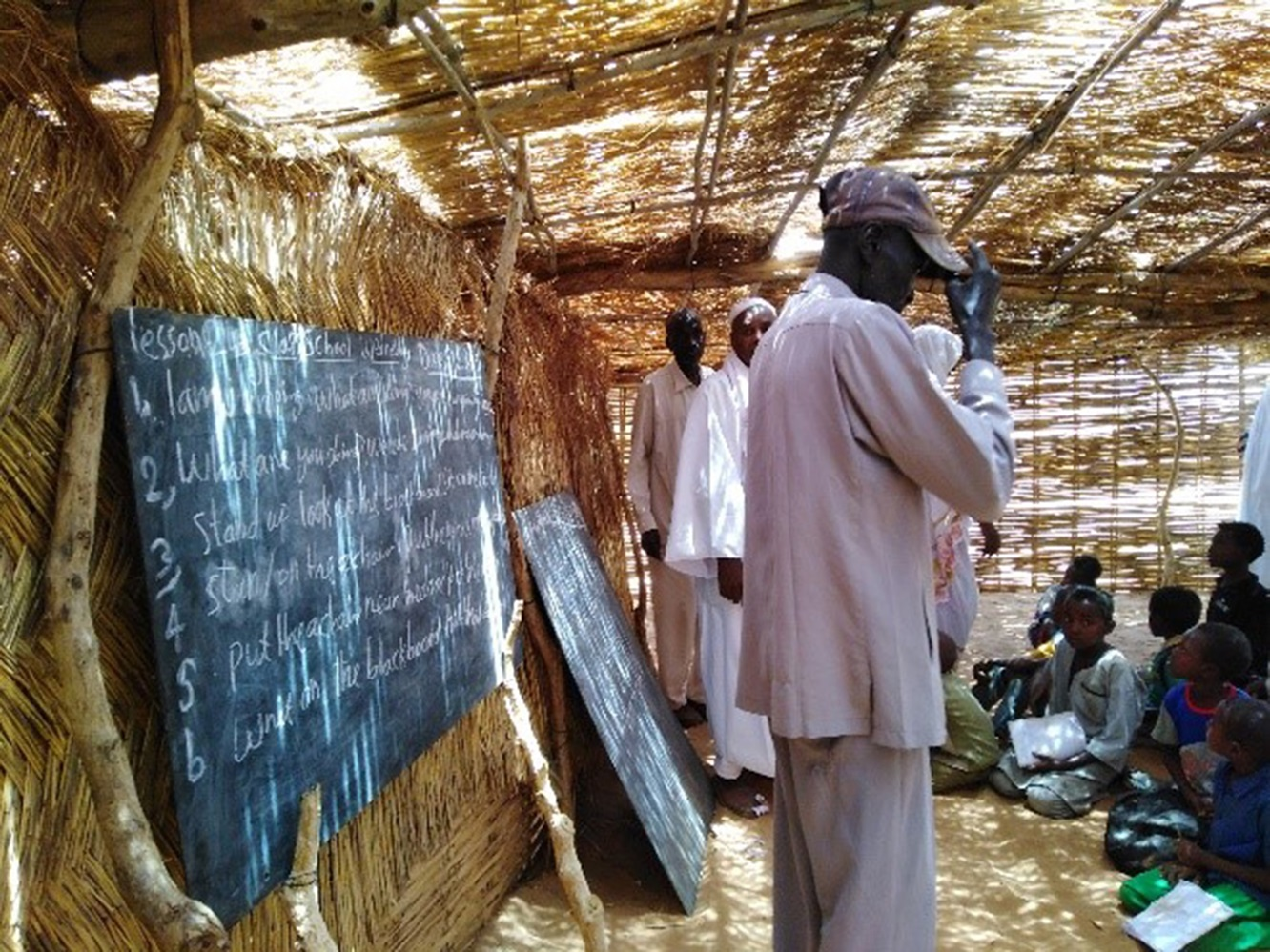 Esta foto de instructores y estudiantes de la actual escuela temporal del campamento de refugiados de Al Nimir, en el estado de Darfur Oriental, demuestra por qué se necesitan más aulas permanentes. Foto por Elrayah, GBGM.