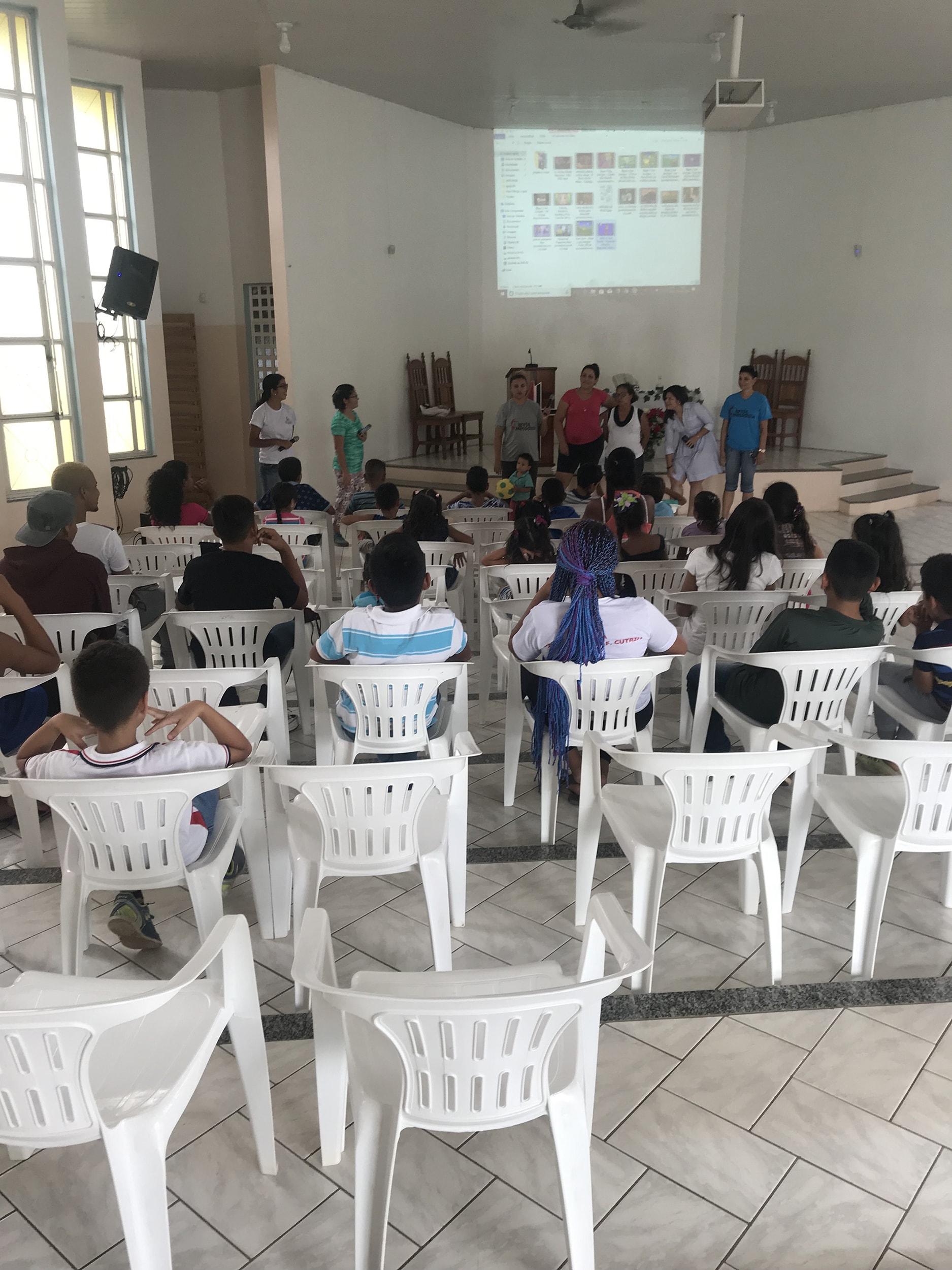 """Los niños venezolanos son bienvenidos en la iglesia antes de que se dividan los grupos para las actividades del programa en Boa Vista, a norte de Brasil. Este ministerio es parte del programa """"Sombra y Agua Fresca"""" para recibir a los/as inmigrantes venezolanos/as en territorio brasileño. Foto por Emily Everett, GBGM."""