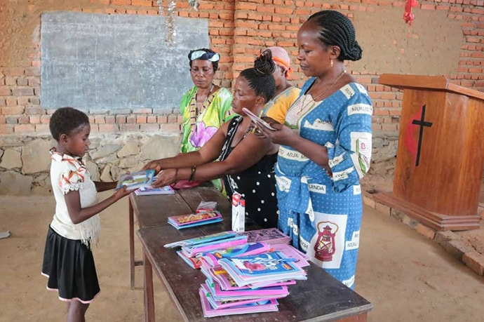 Younger children at the orphanage attend school. This young girl receives a book from the management team which includes Furaha Tshoso (right).  Photo by Chadrack Tambwe Londe, UM News.