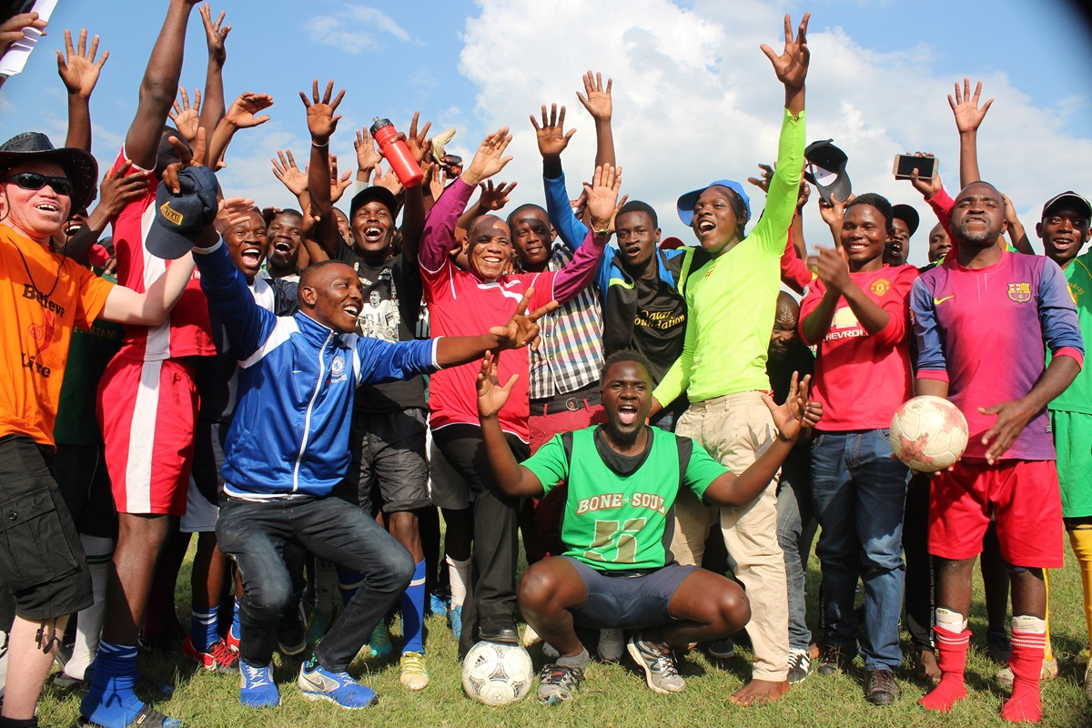 Bishop Eben K. Nhiwatiwa (center, with foot on ball) celebrates with youth teams after playing an exhibition soccer game together at Avonlea Primary School in Harare, Zimbabwe. The Zimbabwe Episcopal Area has put a focus on sports and fitness as a way to get members healthy and bring new souls to Christ. Photo by Kudzai Chingwe, UM News.