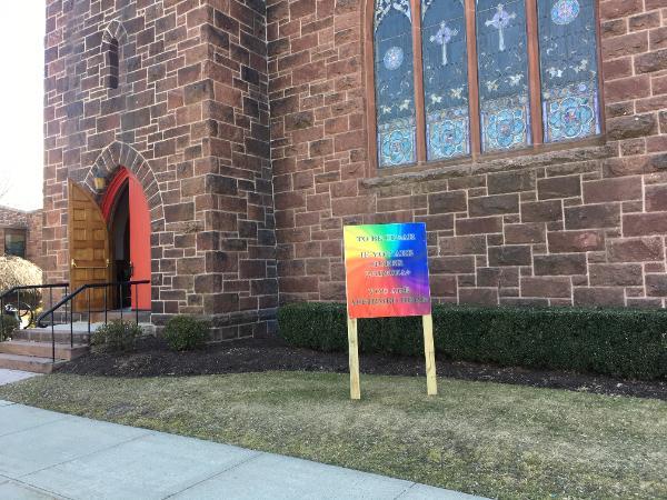 """Desde febrero, un letrero colorido enfrente de la iglesia ha anunciado: """"Para que quede claro si usted es LGBTQ, aquí lo reconocemos!"""". Foto cortesía de la IMU Memorial Mary Taylor."""