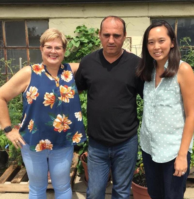 Hace un año, la senadora estatal de Michigan Stephanie Chang (derecha) visitó a Ded en su jardín de la azotea de la iglesia, donde cultiva verduras para la familia y para otras personas. Foto cortesía de la familia Rranxburgaj.