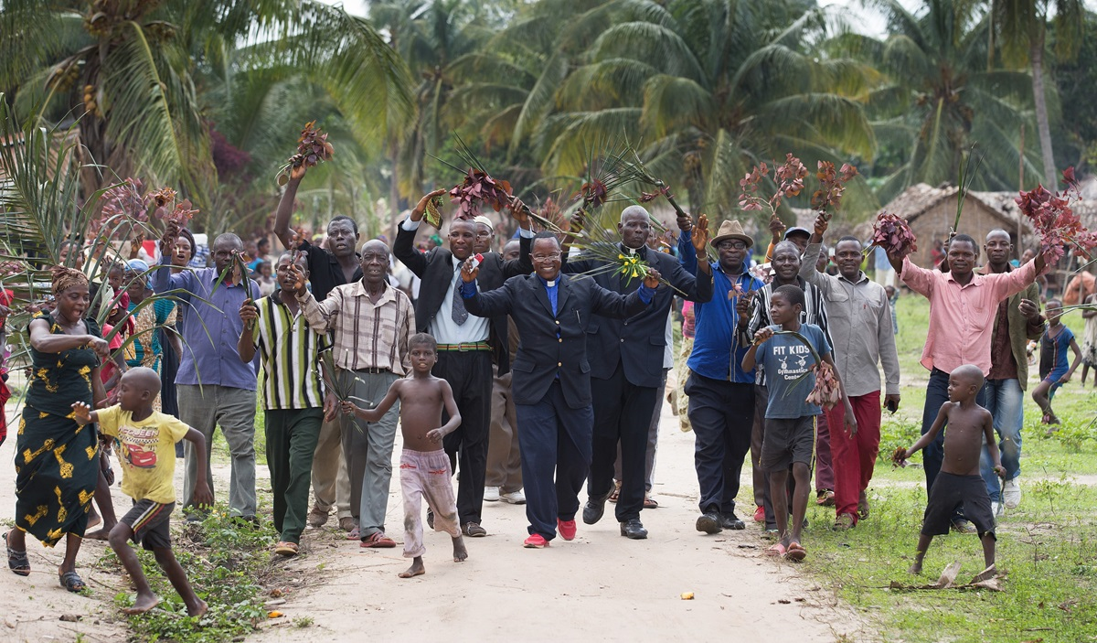 The Rev. Nyenda Okoko (center), a district superintendent, leads a procession of church members as they welcome visitors to Oye United Methodist Church, south of Kindu, Congo, in October 2015. Providing exact membership numbers is difficult in a denomination that spans multiple countries, languages and cultural understandings of church membership. File photo by Mike DuBose, UM News.