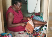 Tapiwa Nyawasha cuts strips from scrap pieces of plastic that she will use to make bed, bath and door mats as a way to increase income and empower widows and single mothers. Tapiwa  is a member of Kuwadzana Extension United Methodist Church in Harare, Zimbabwe. Photo by Chenayi Kumuterera, UM News.