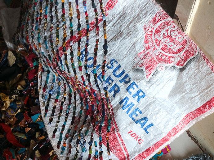 Tapiwa Nyawasha weaves strips of salvaged plastic into household mats. Photo by Chenayi Kumuterera, UM News.