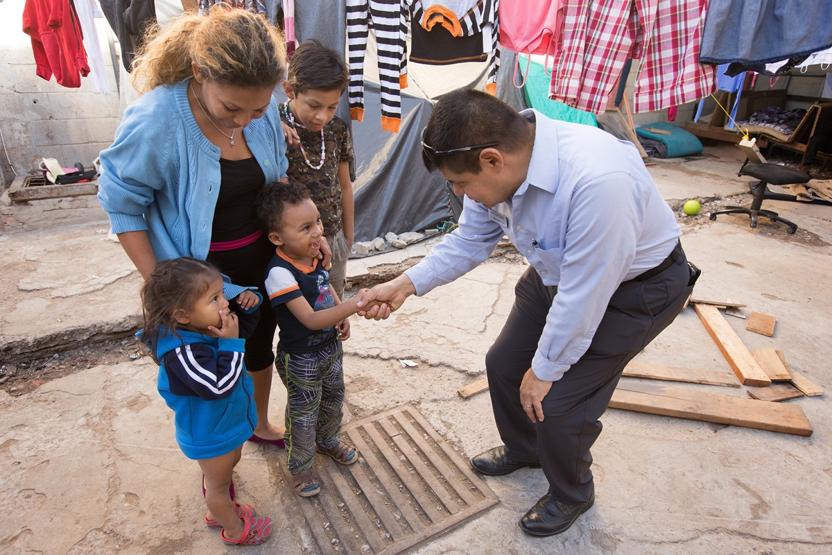The Rev. Joel Hortiales, a United Methodist missionary with the Board of Global Ministries, visits with Lizbeth and her three children, Bridgette, 3, Caleb, 4, and Alvaro Jose, 10, at the Hosanna Refugio Para Mujeres, in Mexicali, Mexico, in December 2018. The family was part of a migrant caravan from Central America. The United Methodist Immigration Task Force is urging support for migrants living in sanctuary churches who have been fined by the federal government. File photo by Mike DuBose, UM News.