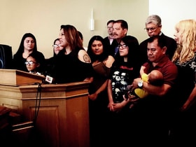 Francisca Lino, who is living in sanctuary at Adalberto United Methodist Church in Chicago, stands with her family and Democratic politicians as well as the Rev. Emma Lozano, pastor of Lincoln United Methodist (far right) during a news conference at the church. Lino is a mother of five U.S. citizen children, wife of a U.S. citizen and has four U.S. citizen grandchildren. Photo by Sara Walker, Lincoln United Methodist Church.