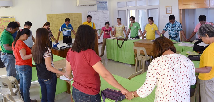 """Staff members and management of the Wesley Savings and Multipurpose Cooperative hold hands in prayer during a meeting at their office in San Isidro, Philippines. The cooperative's purpose is """"to alleviate poverty and enhance the dignity and quality of life of people,"""" said the Rev. Ferdinand J. Valdez, top executive of the cooperative. Photo courtesy of the Rev. Ferdinand J. Valdez."""