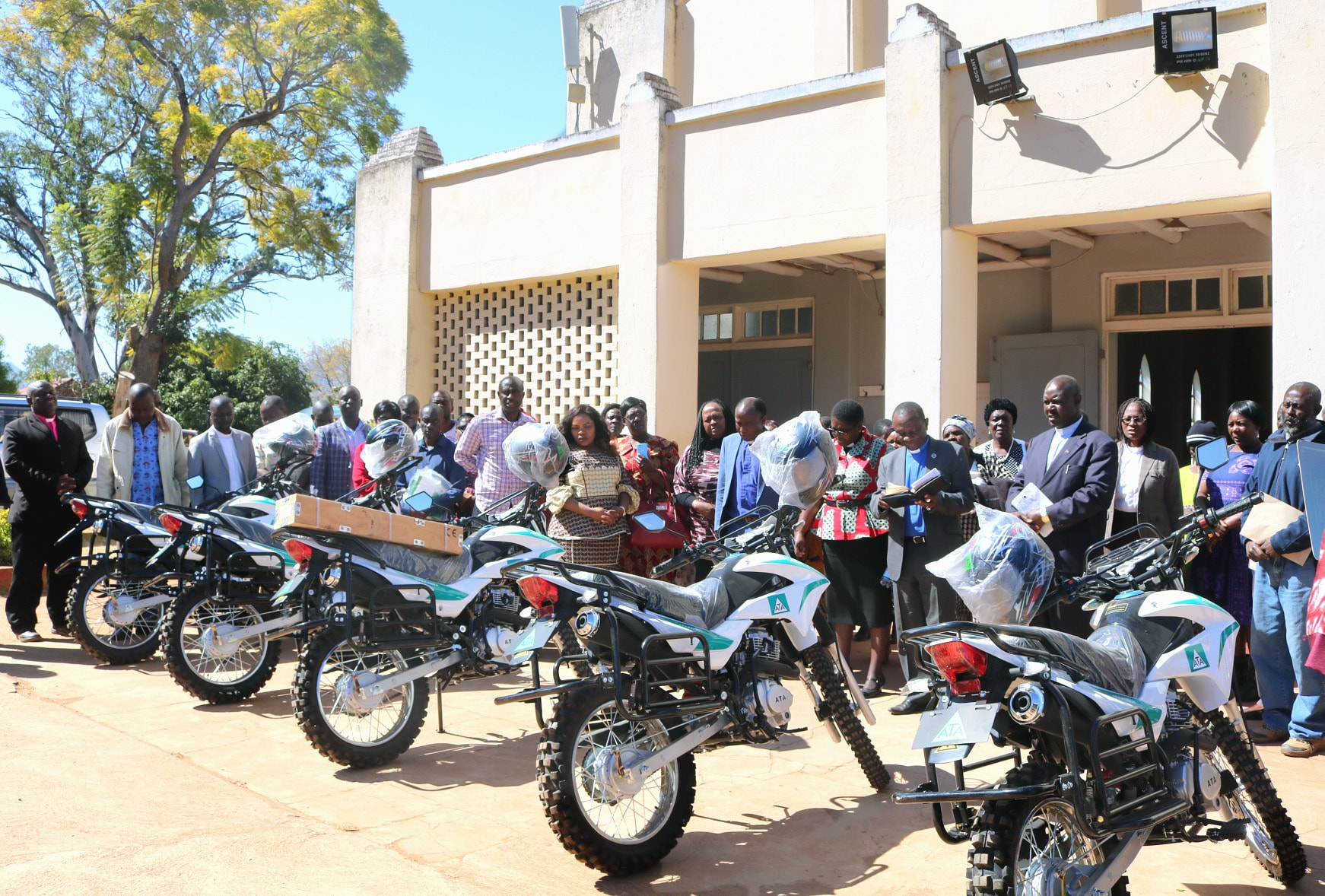 The ministry of five pastors was transformed when they were given motorbikes at a ceremony at Old Mutare Circuit in the Mutasa Nyanga District of Zimbabwe on July 20. The harsh topography makes most of the area inaccessible by traditional motor vehicles. Officiating was the Rev. Alan Masimba Gurupira, administrative assistant to Bishop Eben K. Nhiwatiwa, Zimbabwe Episcopal Area (center right, reading). Photo by Kudzai Chingwe, UM News.