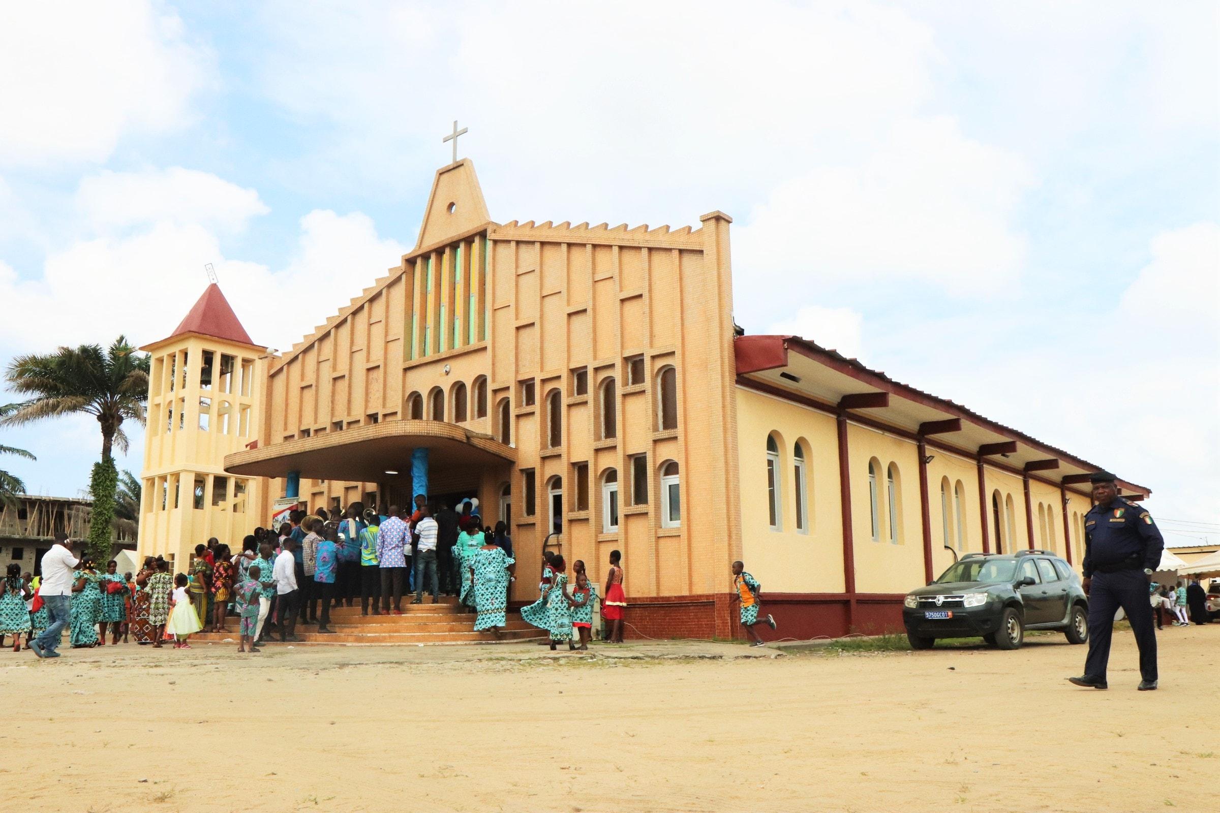 Un policier passe devant le temple de la Cité de grâce d'Anoumabo le jour de la célébration du 25ème anniversaire. Troisième temple construit en matériaux durables depuis l'avènement du Méthodisme dans ce village, il a été dédicacé le 27 février 1994. Photo de Isaac Broune, UM News.