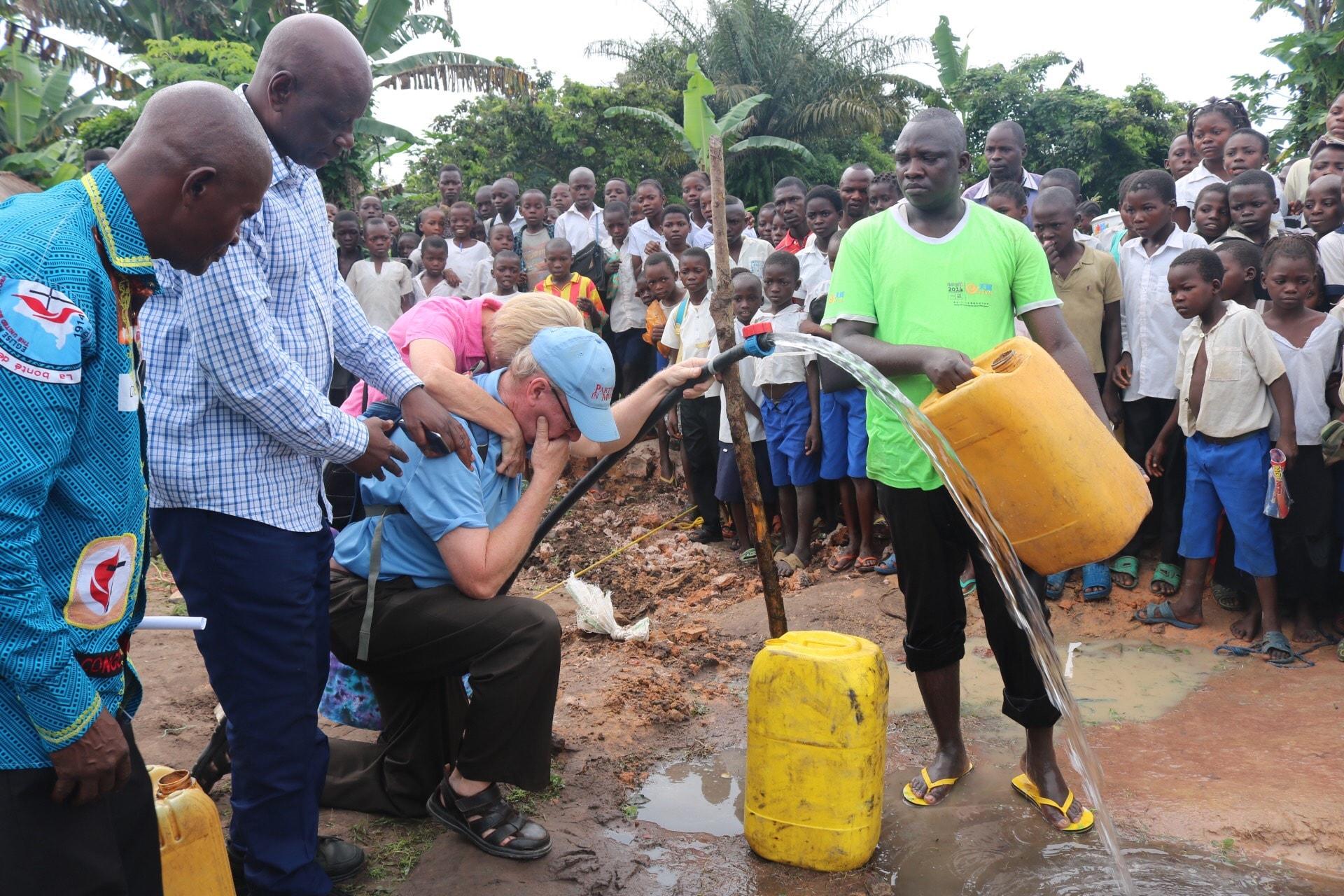 Le couple missionnaire Rev. Jonathan Baker et son épouse Maman Donna sont émus devant les premières sorties d'eau des tuyaux. La population de Wembo-Nyama a longtemps souffert des maladies dues à la mauvaise qualité de l'eau qu'elle consommait. Photo de François Omanyondo, UM News.