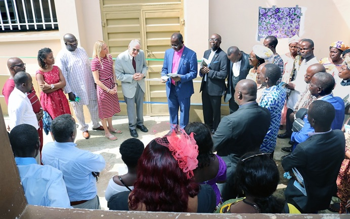 Sierra Leone Area Bishop John Yambasu (center, pink clerical shirt) leads a dedication service in front of the new surgery facility at the Lowell and Ruth Gess United Methodist Eye Hospital in eastern Freetown, Sierra Leone. He is joined by Dr. Lowell Gess (to his right), who started the medical center as Kissy Eye Clinic during his missionary years there. Gess spent 58 of his missionary years in Sierra Leone. Photo by Phileas Jusu, UM News.