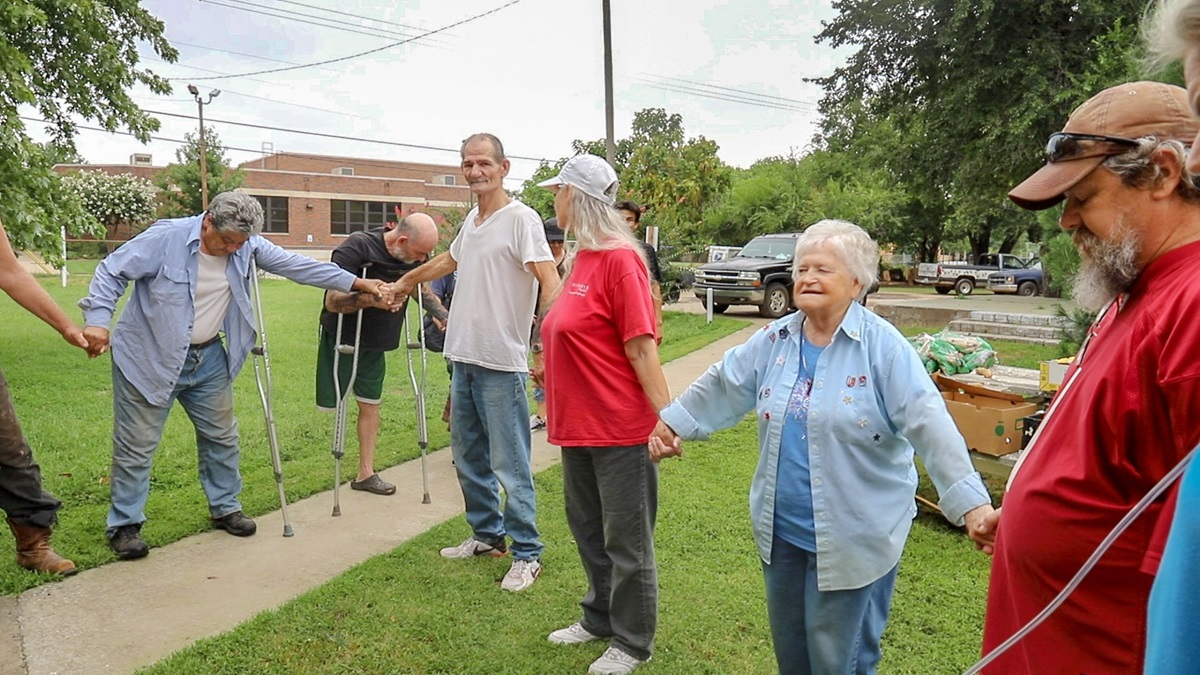 Alfreda Hibbard (second from right), age 81, leads a prayer for participants of the Billy Hooton United Methodist Church food bank in Oklahoma City, Okla. The outreach ministry has helped to feed Oklahoma City residents for nearly 30 years. Photo by Ginny Underwood, UM News.