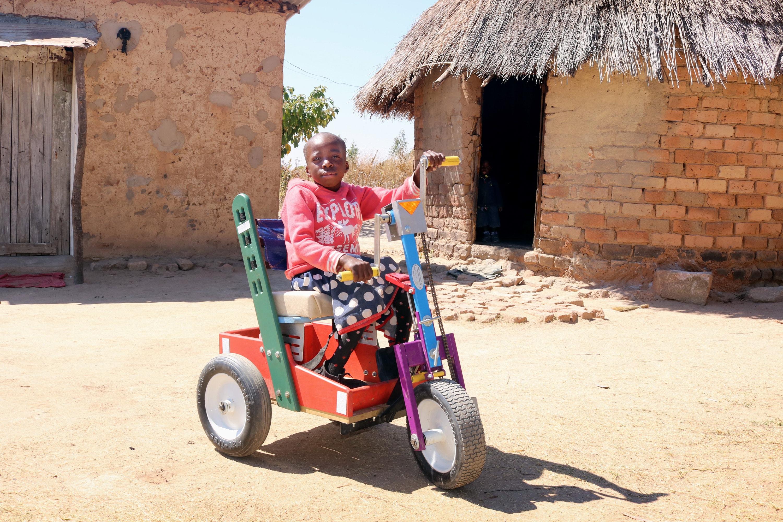 Portia Kasuso, 11, experimenta sua nova cadeira de rodas com pedal manual durante um serviço de reavivamento dos Metodistas Unidos em Murewa, no Zimbábue. O presente da cadeira de rodas foi facilitado pela Conferência Oeste da Igreja no Zimbábue. Foto do Rev. Taurai Emmanuel Maforo, Notícias MU.