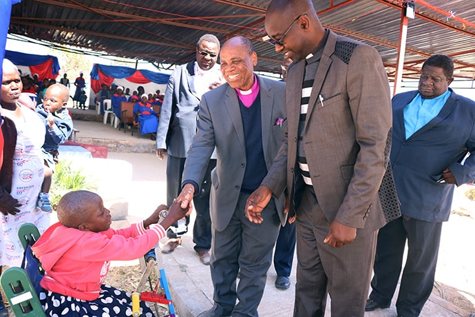 "Portia Kasuso shakes hands with Bishop Eben K. Nhiwatiwa during a United Methodist revival service in Murewa. The young girl was a guest of honor at the service. ""Having Portia at this revival is evidence of how much the church can become a home for all people in spite of their conditions,"" Nhiwatiwa said. Photo by the Rev. Taurai Emmanuel Maforo, UM News."