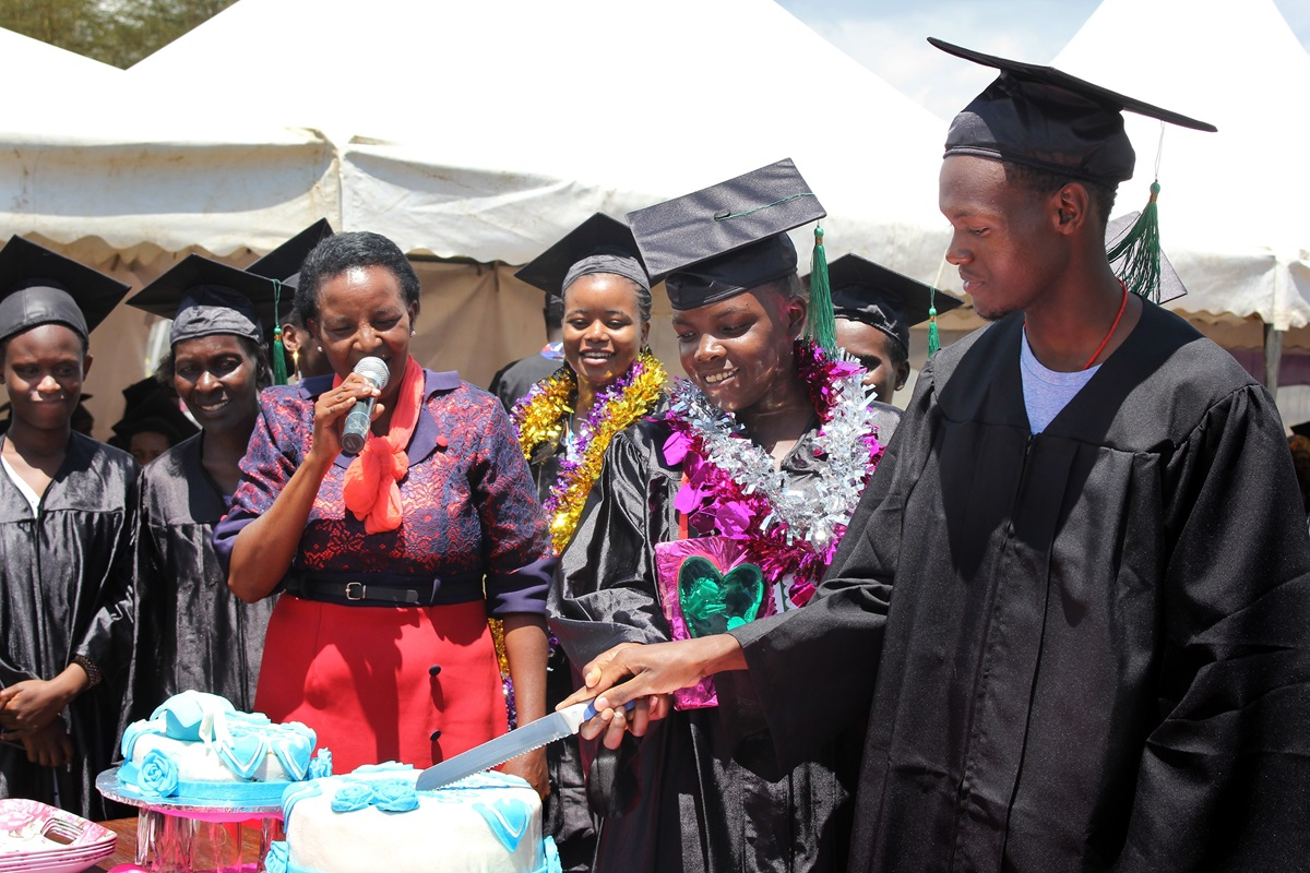 Graduates cut a cake to celebrate their completion of the Inua Partners in Hope vocational training program in Naivasha, Kenya. The program, a partnership between  Trinity United Methodist Church in Naivasha and First United Methodist Church in Winter Park, Fla., teaches vocational and business skills to orphans and vulnerable young people. Photo by Gad Maiga, UM News.