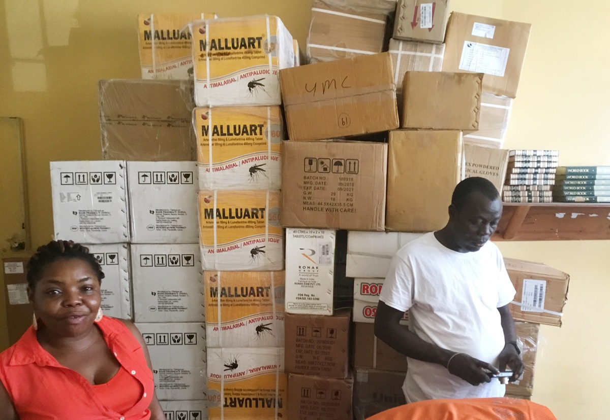 Laurine Deemi and Thomas Mallah stand in front of medical supplies at The United Methodist Church in Liberia's health department in Monrovia, Liberia. The United Methodist Board of Global Ministries has donated over $40,000 worth of anti-malarial medicine, tests and mosquito nets to the church in Liberia. Photo by E Julu Swen, UM News.